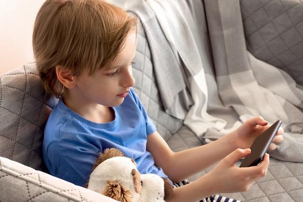 Дистанционное обучение онлайн, образование и работа. ребенка учат дистанционно из дома. мальчик руки держат мобильный телефон
