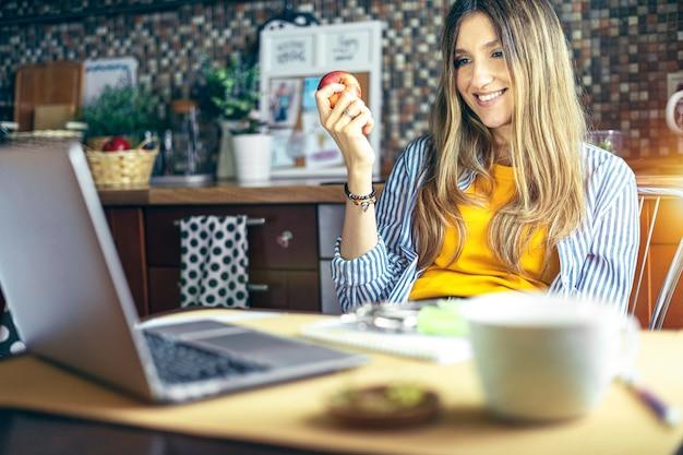 Дистанционное обучение онлайн-образование и работа женщина с яблоком, имеющая видеозвонок, счастлива и улыбается