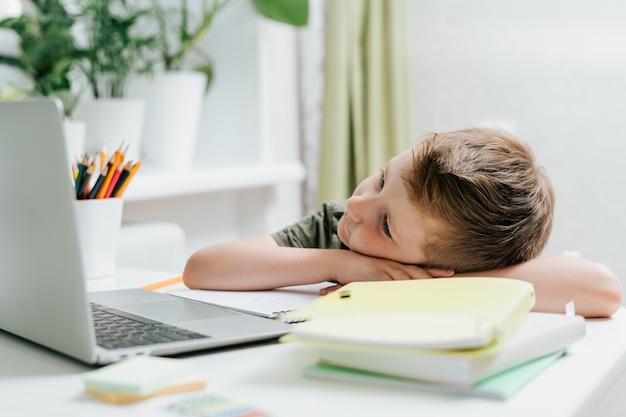 Дистанционное обучение онлайн-образование кавказский мальчик учится дома за ноутбуком, усталый сон и дремота