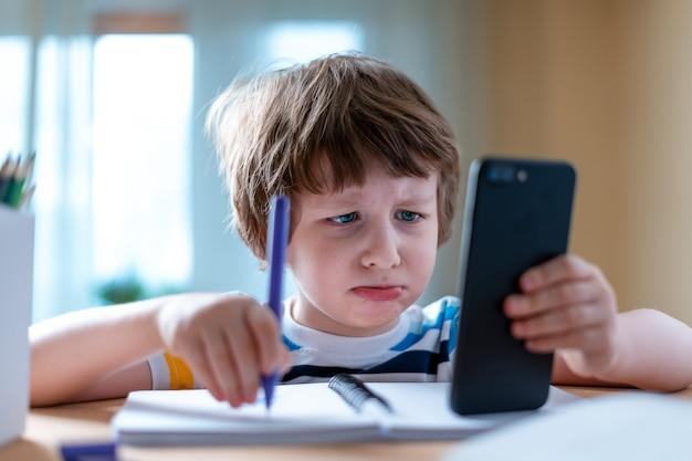 Дистанционное обучение онлайн-образование кавказский грустный мальчик учится дома со смартфоном и делает