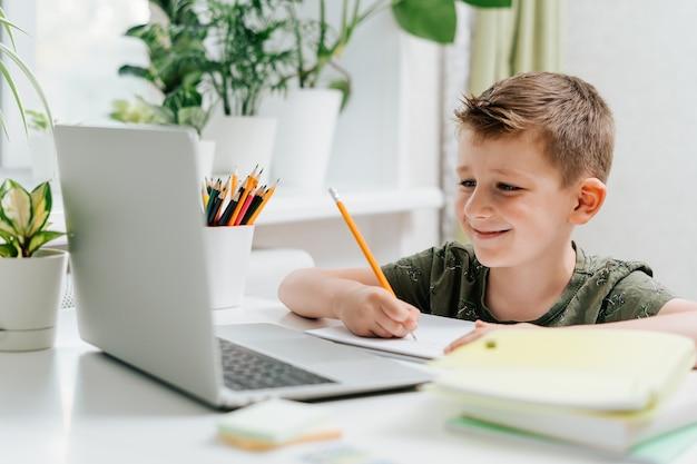 Дистанционное обучение онлайн-образование кавказская улыбка ребенок мальчик учится дома с ноутбуком и делает