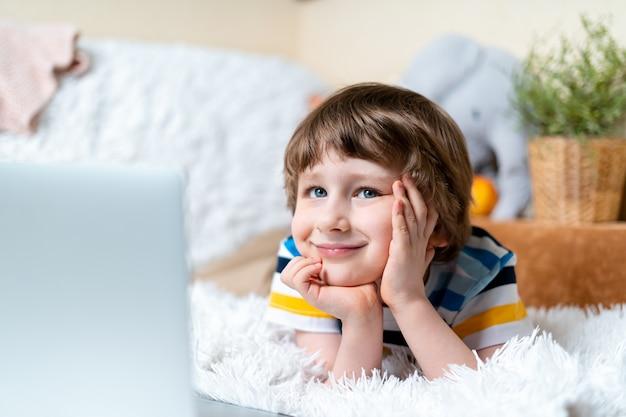 Дистанционное обучение онлайн-образование кавказская улыбка мальчик учится дома с планшетным ноутбуком