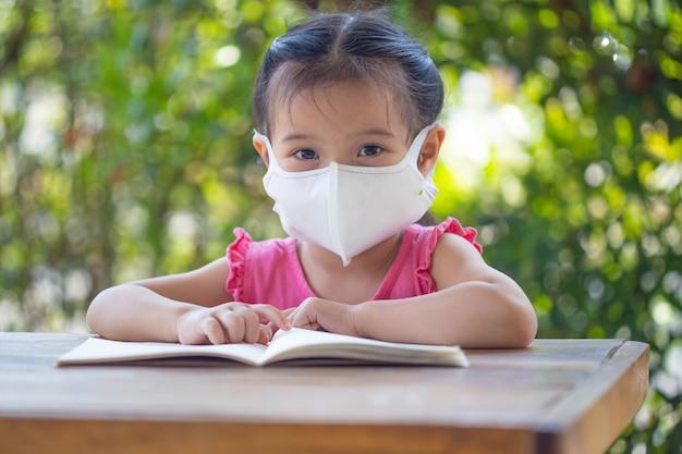 Дистанционное обучение онлайн-образование. ребенок в маске, чтобы посмотреть онлайн-урок.