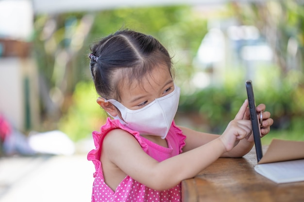 Distance learning online education. child in a mask to watch an online lesson.