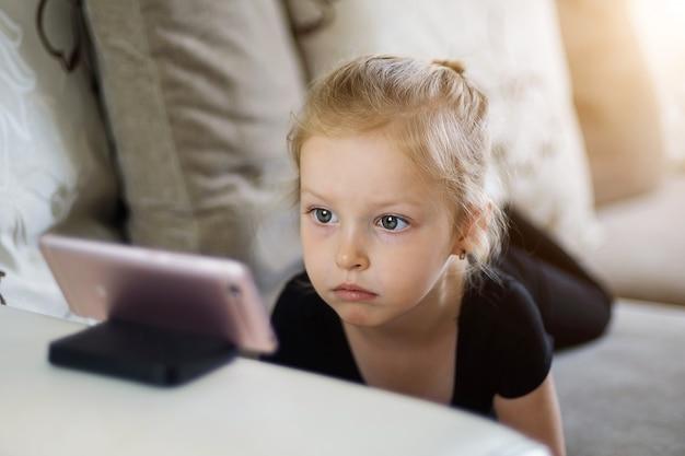 원격 교육, 어린이를위한 온라인 교육. 전화 앞에서 집에서 공부하는 어린 소녀. 아이 온라인 만화, 아이 컴퓨터 중독, 보호자 통제 개념을보고.