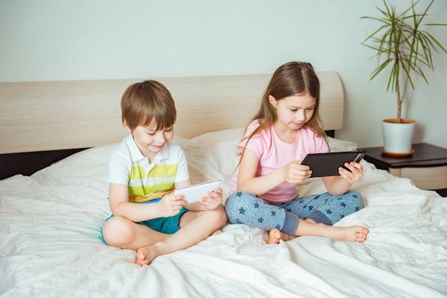 원격 교육 온라인 교육. 방에있는 침대에 태블릿과 함께 앉아있는 아이들
