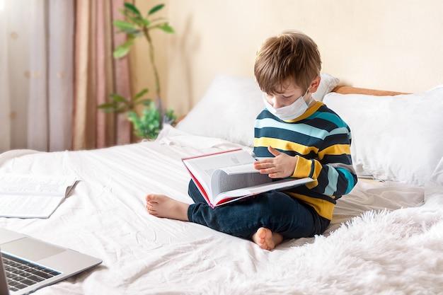 원격 교육 온라인 교육 검역 소년에서 공부하는 의료 마스크에 책과 노트북