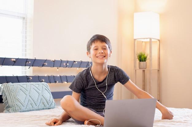 遠隔教育オンライン教育男子生徒が自宅で勉強し、学校の宿題をしている