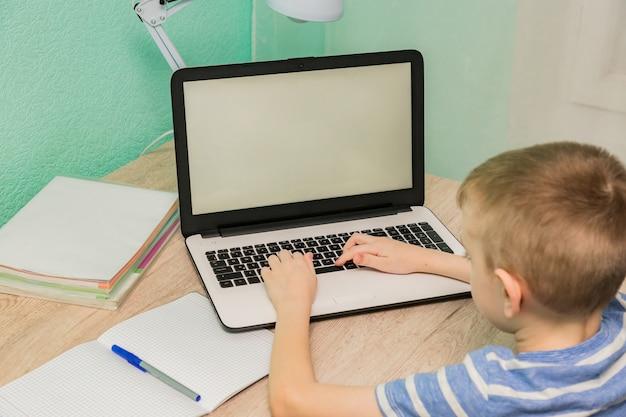 Дистанционное обучение онлайн-образование. школьник учится на дому с ноутбуком ноутбука и делать домашнее задание школы.