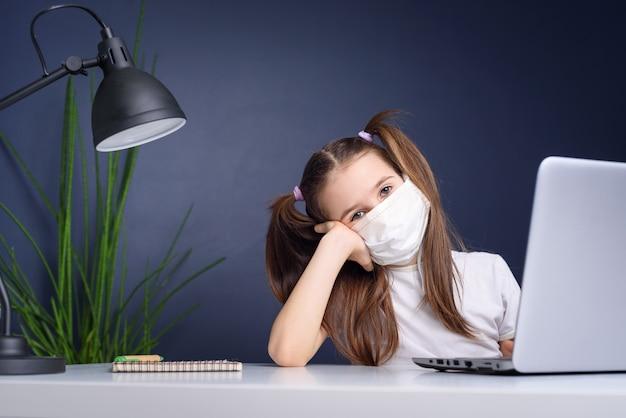 オンライン教育の遠隔学習。自宅で勉強して、ラップトップのノートブックで働いて、学校の宿題をしている医療マスクの女子高生。コロナウイルス検疫の概念