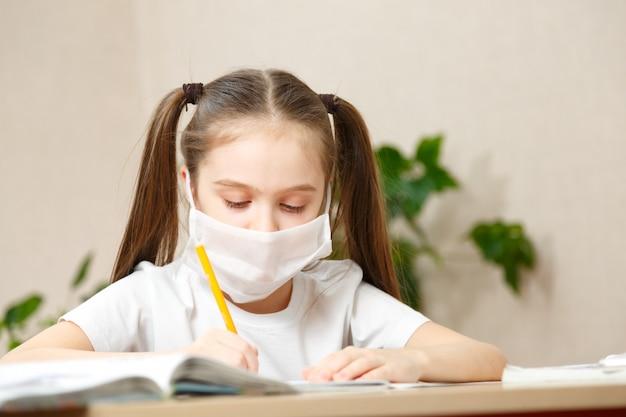 オンライン教育の遠隔学習。自宅で勉強して医療マスクの女子高生、