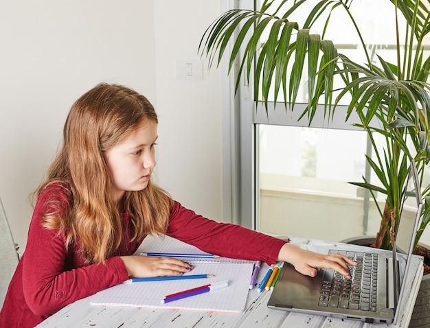 オンライン教育の遠隔学習。ノートパソコンで自宅で勉強し、学校の宿題をしている女子高生。テーブル上のトレーニングノートブックと色付きのフェルトペン