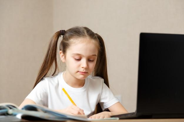 オンライン教育の遠隔学習。自宅で勉強している女子高生