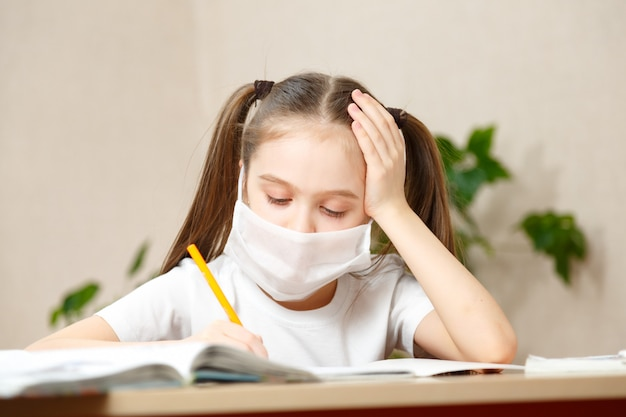 Distance learning online education. sickness schoolgirl in medical mask studying at home, doing school homework. training books and notebooks on table