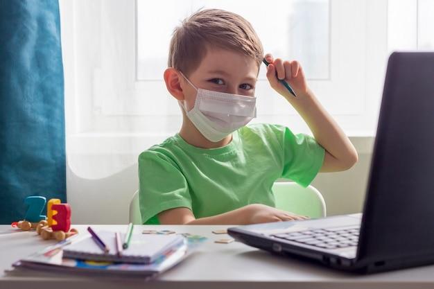 遠隔学習、オンライン教育。隔離期間中の社会的距離、自己隔離。未就学児またはラップトップで自宅で勉強して、開発学校の宿題をしている医療用マスクの男子生徒