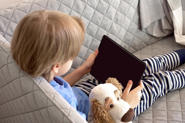 Distance learning online education and work. child study remotely from home on the couch. boy hands hold tablet.