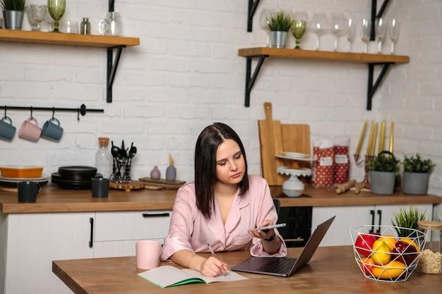 Дистанционное обучение онлайн. подготовка к экзаменам. женщина с телефоном в руках сидит за компьютером и что-то пишет. удаленная работа.