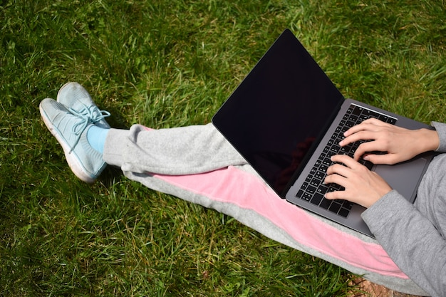 Distance learning outdoor. child working at laptop in garden. online learning by internet.