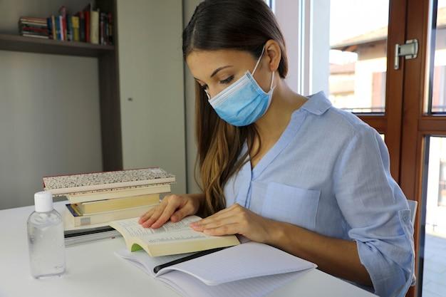 Карантин для дистанционного обучения: молодая женщина читает и учится на дому на предмет вирусного заболевания 2019-ncov.