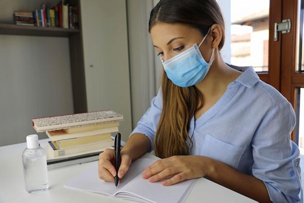 自宅でウイルス病2019-ncovについて勉強している遠隔学習検疫の若い女性。