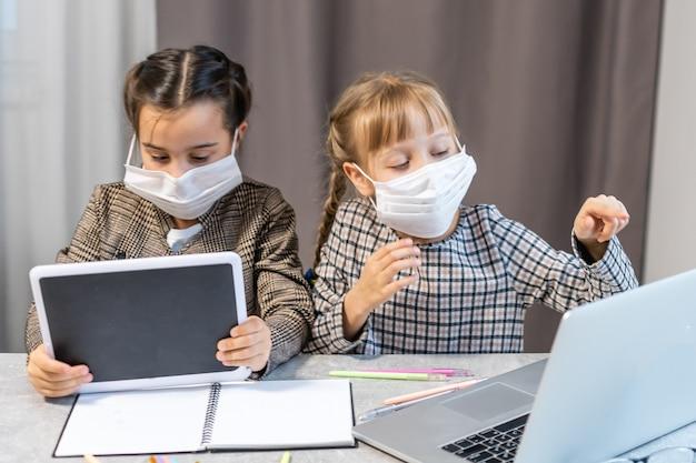 Дистанционное обучение. школьницы за ноутбуком в маске изучают онлайн, сидя за столом дома