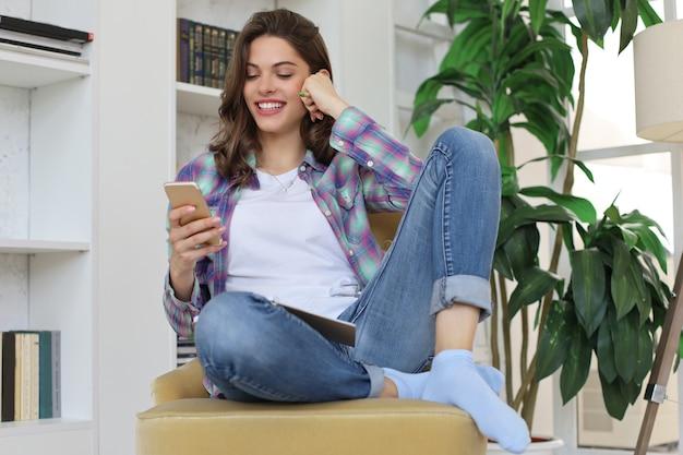 원격 학습. 공부하기 전에 소셜 미디어를 확인하는 젊은 여학생, 책 더미로 둘러싸인 아늑한 국내 인테리어에 대한 의자에 앉아