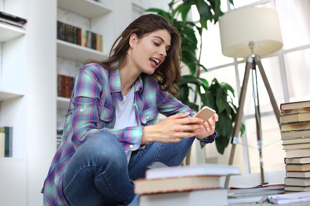 원격 교육. 공부하기 전에 소셜 미디어를 확인하는 젊은 여학생, 책 더미로 둘러싸인 아늑한 국내 인테리어에 대해 바닥에 앉아