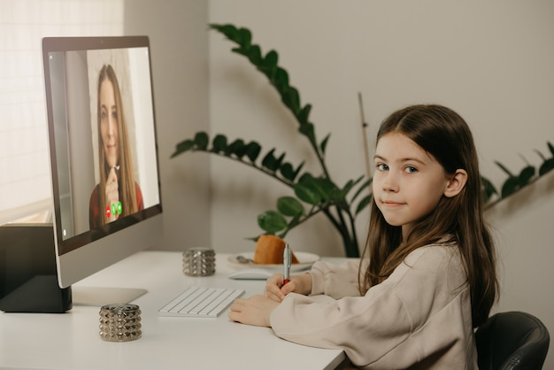 Distance learning. a young girl with long hair studying remotely from her female teacher online. a pretty child learns a lesson using a desktop computer at home. home education.