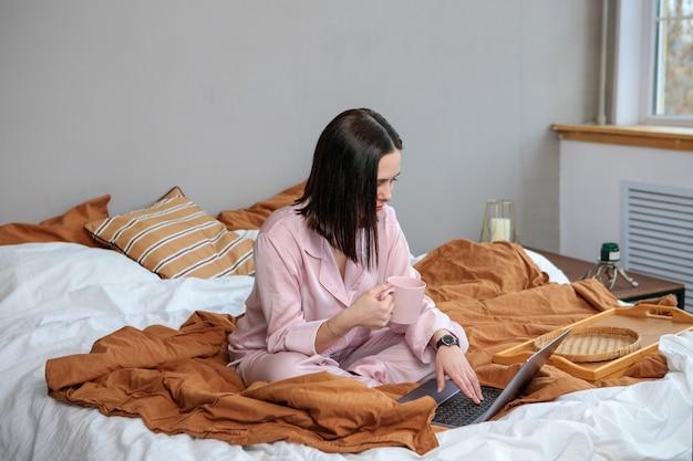거리 온라인 work.happy 여자 여자 작업 사무실 침대에 집에서 원격으로 작업. 컴퓨터를 사용하고 커피를 마시는 것.