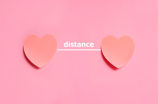 Distance text placed between two hearts made from paper on the pink background