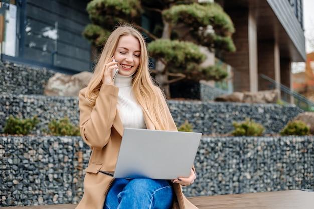 Дистанционная работа. деловая молодая блондинка женщина сидит на скамейке с мобильным телефоном и ноутбуком, разговаривает по телефону и работает на фоне офисного здания