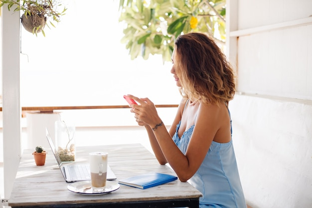 Distance work concept woman in summer cafe with laptop