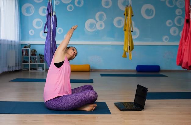 Дистанционная йога женщина занимается с ноутбуком в студии