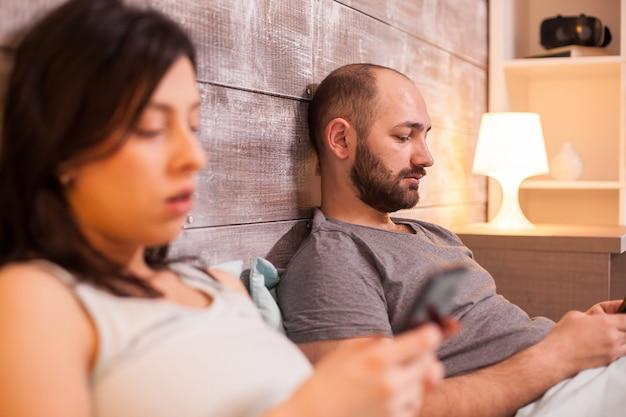 スマートフォンを使用して就寝前にベッドで遠いカップル。