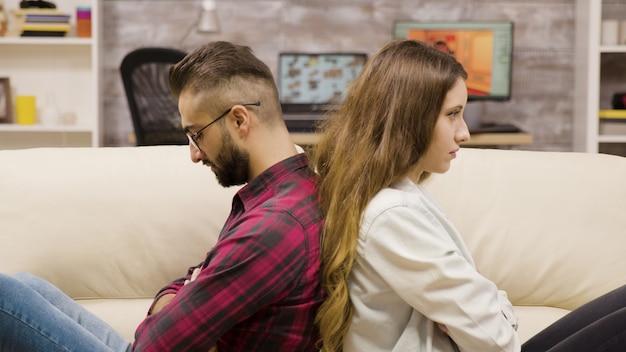 議論の後、ソファに背中合わせに座っている遠いカップル。ボーイフレンドとガールフレンドの問題。