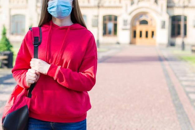 원격 학습 개념입니다. 대학 건물에서 떠나는 배낭을 들고 캐주얼한 빨간 스웨터를 입은 불행한 슬픈 10대 소녀의 클로즈업 사진
