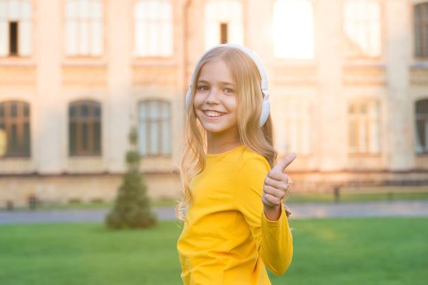 遠隔教育。ヘッドフォンを身に着けている幸せな少女。ステレオサウンド。良い話を聞く。独学。ワイヤレステクノロジーを搭載したヘッドフォン。音楽を聴いている小さな子供現代のイヤホン。