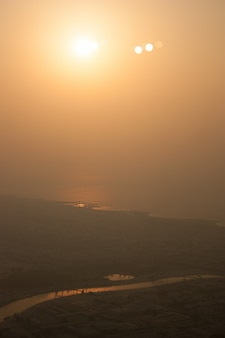 Отдаленный снимок реки, протекающей недалеко от города в дневное время с ярко сияющим солнцем в небе