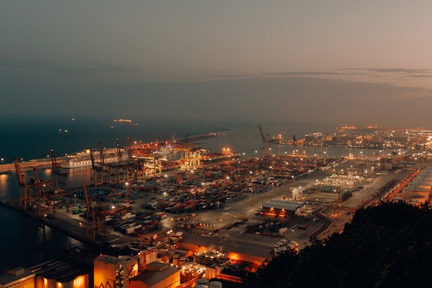 Distant shot of a port with boats loaded with cargo and shipment during nighttime