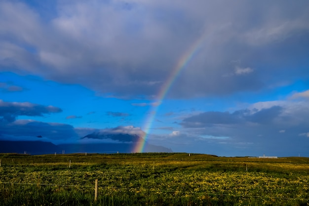 Distant shot of a rainbow over horizon above a grass field in a cloudy sky