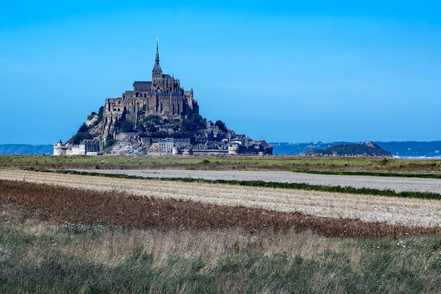 Distant view of mont saint michel sticking out on the horizon