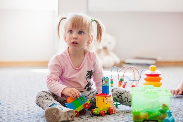Ragazza distratta con i giocattoli che guardano lontano