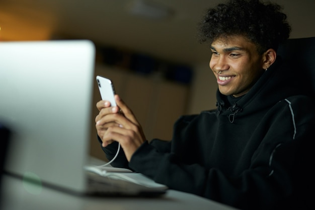 공부하는 동안 웃고 스마트폰을 사용하는 행복한 남학생의 주의를 산만하게 하는 초상화
