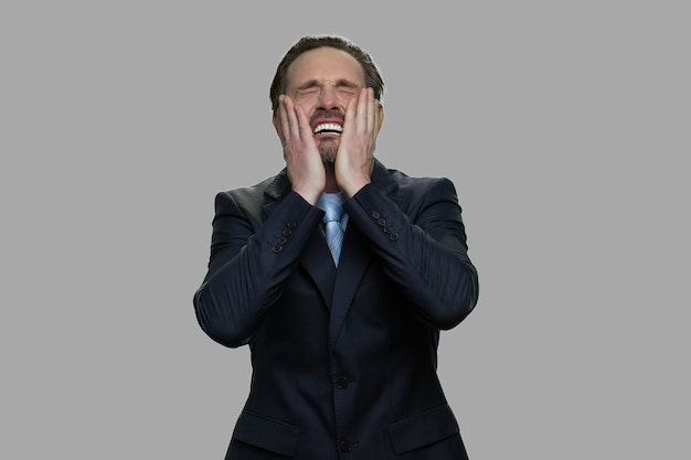 取り乱した灰色の背景にビジネスマンを強調しました。圧倒された落ち込んだビジネスマン。破産の概念。