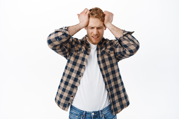 Distressed adult redhead man having headache, holding hands on head and looking upset, disappointed or frustrated of failure, standing over white wall