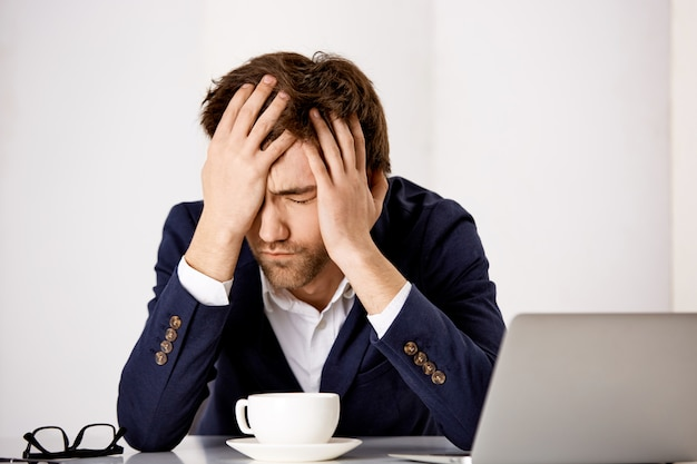 고민과 생각에 잠겨있는 젊은 슬픈 남성 기업가, 남자는 문제가 작동, facepalm, 눈을 감고 우울