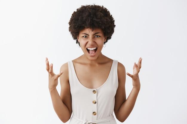 Расстроенная и рассерженная женщина находится под давлением, кричит и сжимает руки от гнева, гримасничает и хмурится, споря