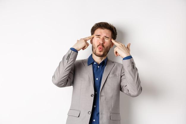 Обеспокоенный и напряженный бизнесмен, указывая на голову и жалуясь, чувствуя раздражение из-за ситуации, взорвавшей его разум, встревоженно стоит на белом фоне.
