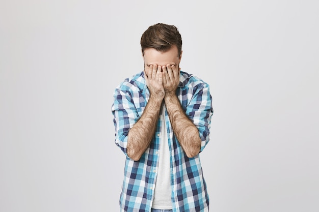 苦痛と疲れの中年男性のフェイスパーム