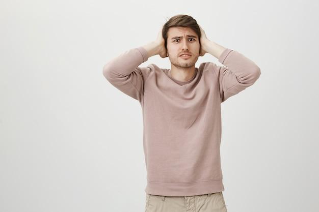 悩んで困った男は耳をふさいで、困った顔をしている
